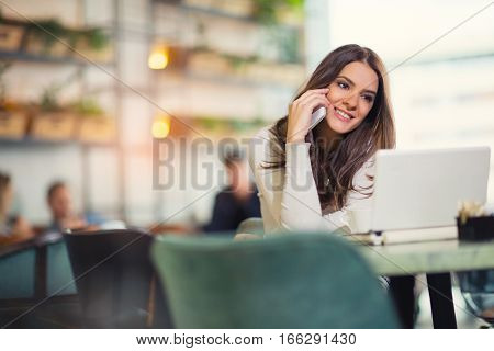 Young gorgeous woman having smart phone conversation while sitting in front of open laptop computer in cafe bar