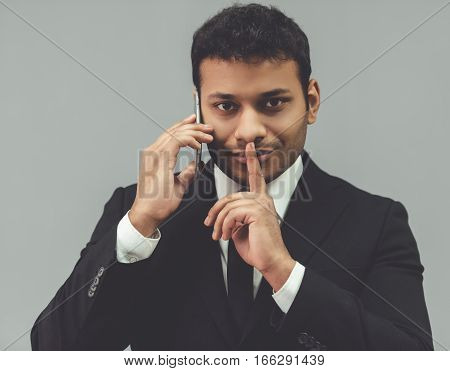 Attractive Afro American businessman in classic suit is talking on the mobile phone and showing silence sign on gray background