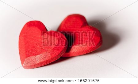 A pair of red wooden hearts isolated on white.