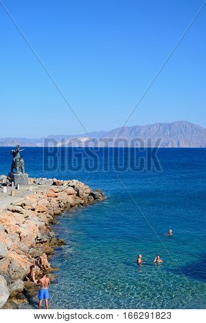 AGIOS NIKOLAOS, CRETE - SEPTEMBER 17, 2016 - Tourists cooling off in the shallow sea with the statue of Europe sitting on a bull to the left hand side Agios Nikolaos Crete Greece Europe, September 17, 2016.
