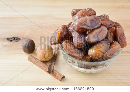 Lot of dates in glass bowl on ash tree wooden table together witfh cinnamon and pair of nutmegs