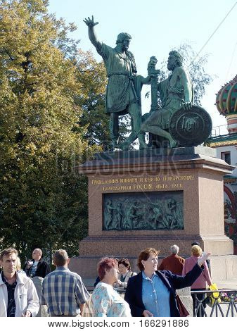 MOSCOW - SEPTEMBER 26, 2007: Tourists walk on Red Square near monument to leaders of Second People's Militia in years of the Smoot Minin and Pozharsky. Inscription on monument: