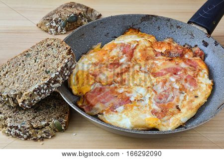 Strong breakfast fried bacon and eggs in old frying pan and healthy chrono bread with seeds