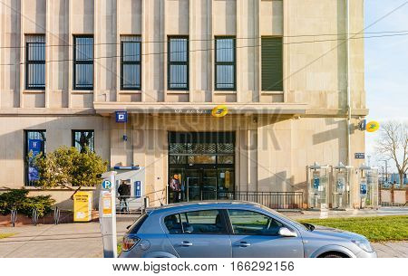 MULHOUSE FRANCE - DEC 12 2015: La Poste post office branch in the heart of Mulhouse France with people sending letters and withdrawing money from La Banque Postale ATM. La Poste is France's leading employer with a total workforce of 300 000 working in pos