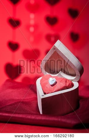 A romantic valentine still life theme gift of a diamond heart in a wooden heart shaped box.