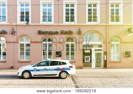 MULHOUSE FRANCE - DEC 12 2015: Banque Kolb on French street with French police car patrolling the empty street on a warm summer day . Banque Kolb is part of Societe Generale