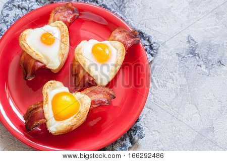 Baked egg breakfast with bacon and toast heart shape for Valentine day