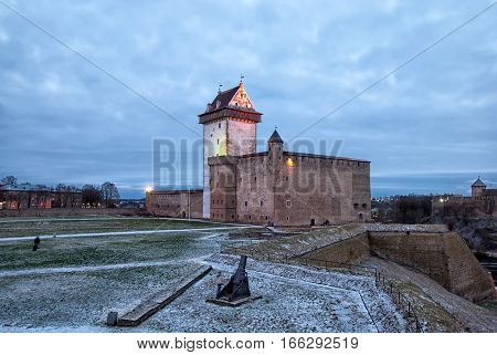 NARVA, ESTONIA - JANUARY 2, 2017: Night view of Hermann Castle Museum and mortar on the courtyard. On the right side is fragment of Ivangorod Fortress in Russia on the other bank of The Narova River