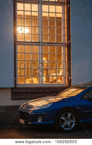 STRASBOURG FRANCE - MAR 18 2016: French Peugeot car parked near an illuminated French window with silhouettes of people inside