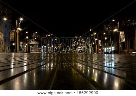 Barcelona Spain - December 1 2016: La Rambla street at night in Barcelona Spain. Unidentified people visible.