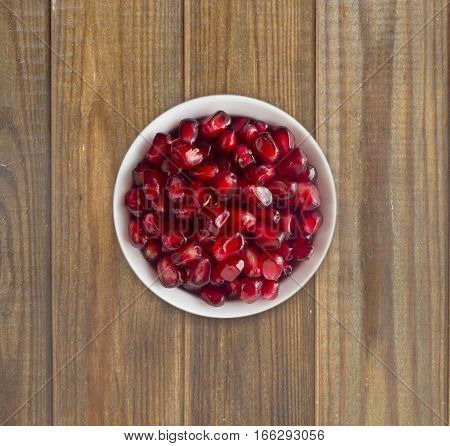 Pomegranate seeds on a wooden background. Red grains of a pomegranate in ceramic bowl. Top view.