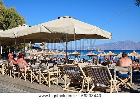 AGIOS NIKOLAOS, CRETE - SEPTEMBER 17, 2016 - Tourists relaxing on the beach with beachside restaurants in the foreground Agios Nikolaos Crete Greece Europe, September 17, 2016.