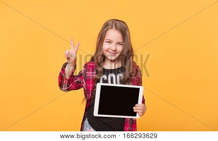 Happy child with tablet computer. Kid girl showing tablet screen isolated over yellow color background. Happy little girl student with empty display concept