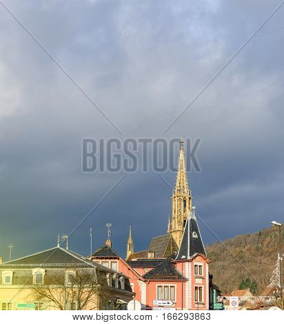 Majestic spire of Collegiale Saint-Thiebaut (Saint-Theobald collegiate church) in Thann Haut-Rhin peacefully watching the city of Thann on a warm winter day with dark cloud approaching in the background