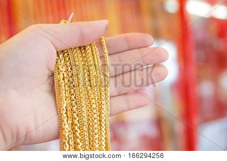 Hand holds lot of neclace gold jewelryOLYMPUS DIGITAL CAMERA