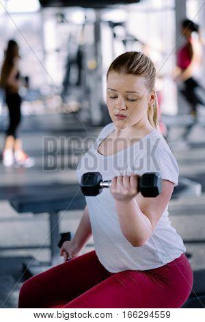 Beginner chubby girl exercising in fitness club