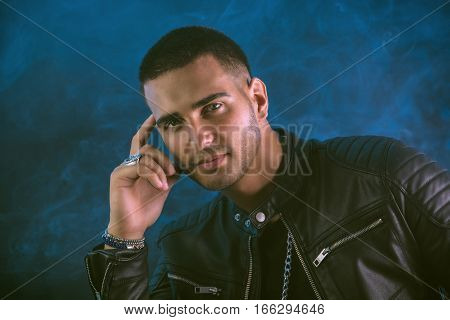 Attractive young man with black leather jacket. Smoke and dark background in studio. Head and shoulders shot