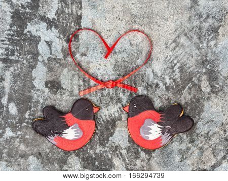 Gingerbread cookie in the shape of birds bullfinches hearts red ribbon love valentine day concept. Sweet cookies bullfinches on a gray grunge background