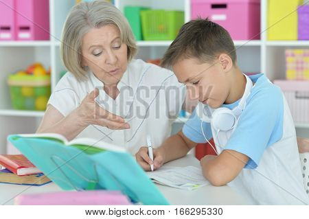 Portrait of a granny with her grandson doing lessons