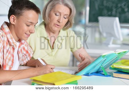 Portrait of a granny with her grandson doing homework