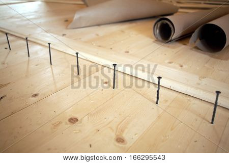 Installation of the floor in a house. Screws lined up before tightening diagonal view closeup
