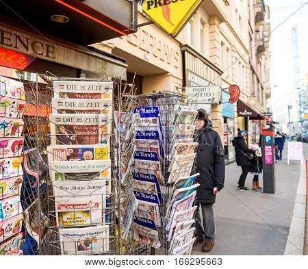 PARIS FRANCE - JAN 21 2017: Man purchases International newspapers from a kiosk newsstand featuring headlines with Donald Trump inauguration as the 45th President of the United States in Washington D.C