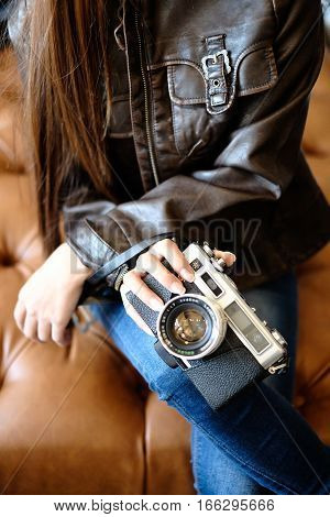Girl holding vintage camera in her hands