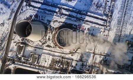 Heat electric station in winter. Aerial view. From above. Power station in a forest in sunny weather. Top view