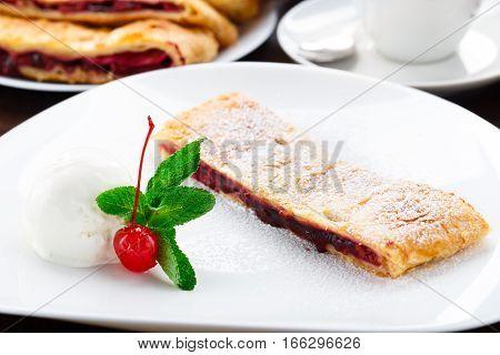Cherry strudel with vanilla ice cream on a plate