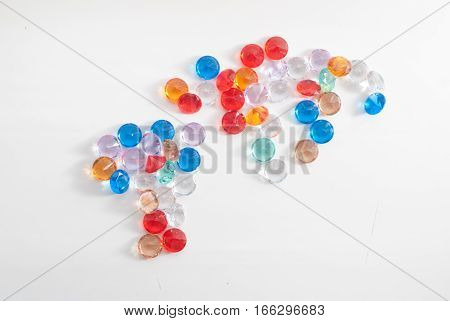 A collection of different faceted stones on a white background, gemstones in the shape of the continents