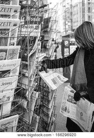 PARIS FRANCE - JAN 21 2017: Woman purchases a Le Monde French newspaper from a newsstand featuring headlines with Donald Trump inauguration as the 45th President of the United States in Washington D.C