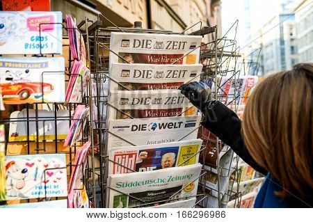 PARIS FRANCE - JAN 21 2017: Woman purchases a Die Zeit German newspaper from a newsstand featuring photos and headlines with Donald Trump inauguration as the 45th President of the United States in Washington D.C