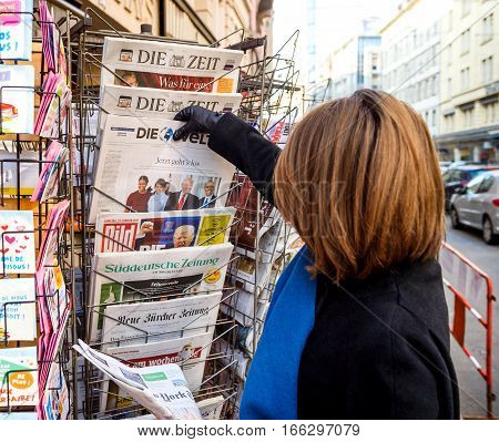 PARIS FRANCE - JAN 21 2017: Woman purchases a Die Welt German newspaper from a newsstand featuring headlines with Donald Trump Barack Obama Melania Trump and Michele Obama at inauguration as the 45th President of the United States in Washington D.C
