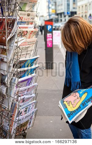 PARIS FRANCE - JAN 21 2017: Woman purchases Charlie Hebdo Le Monde newspaper from a newsstand featuring headlines with Donald Trump inauguration as the 45th President of the United States in Washington D.C