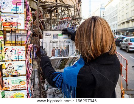 PARIS FRANCE - JAN 21 2017: Woman purchases a The New York Times newspaper from a newsstand featuring headlines with Donald Trump Barack Obama Melania Trump and Michele Obama at inauguration as the 45th President of the United States in Washington D.C