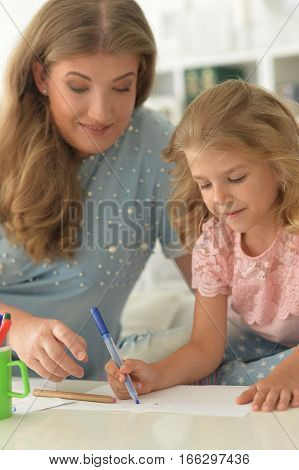 mother with daughter doing homework, together at home