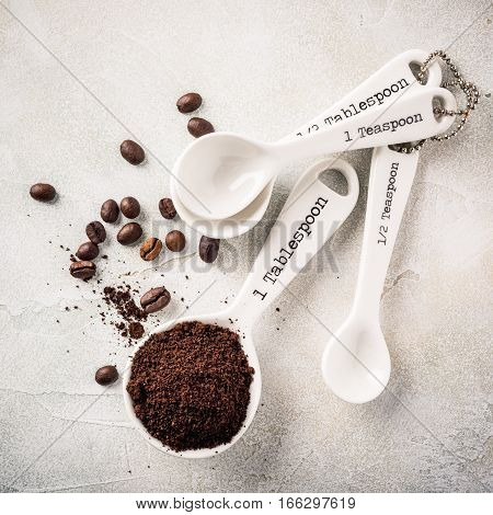 Measuring spoons with ground coffee, retro style toned, copy space, top view.