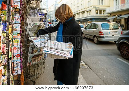 PARIS FRANCE - JAN 21 2017: Woman looking and purchases Het Laastste Nieuws Dutch newspaper from a newsstand featuring headlines with Donald Trump inauguration as the 45th President of the United States in Washington D.C holding stack of press newspaper