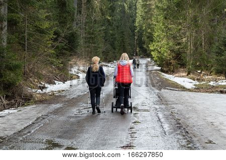 Tourists walking on hiking path in Chocholowska valley in spring season Tatra Mountains Poland