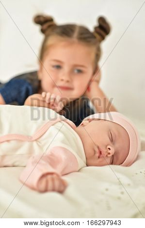 girl with her newborn sister close up