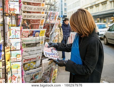 PARIS FRANCE - JAN 21 2017: Woman purchases a Bild German newspaper from a newsstand featuring headlines with Die Trump Show of Donald Trump inauguration as the 45th President of the United States in Washington D.C