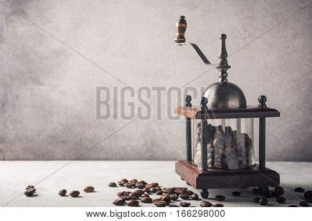 Retro coffee mill with beans, retro style toned, copy space.