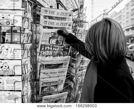 PARIS FRANCE - JAN 21 2017: Woman purchases a Bild German newspaper from a newsstand featuring headlines with Die Trump Show of Donald Trump inauguration as the 45th President of the United States in Washington D.C - black and white