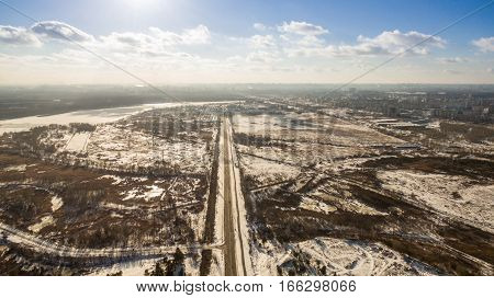 Panorama of forest with highway in the middle on a background of urban development in winter on a sunny day. Aerial view.