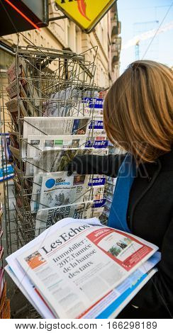 PARIS FRANCE - JAN 21 2017: Woman holding stack pf newspapers buying USA TODAY WEEKEND newspaper from a newsstand featuring headlines with Donald Trump inauguration as the 45th President of the United States in Washington D.C