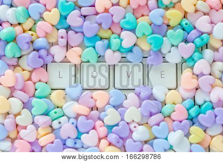 Love concept LOVE text on white keyboard buttons with small colorful pastel heart shaped beads border.