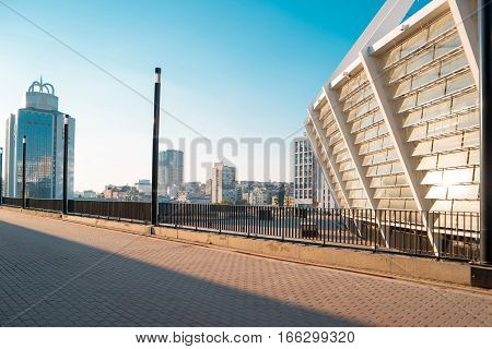 City at daytime. Buildings and blue sky. Stadium and business center.