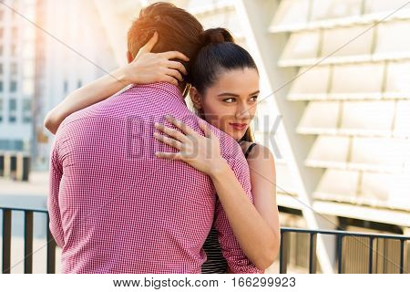 Young woman hugging man. Guy and girl outdoors. Feelings get stronger.