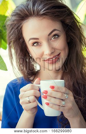 Woman Drinking Coffe In A Cafe Looking At The Camera