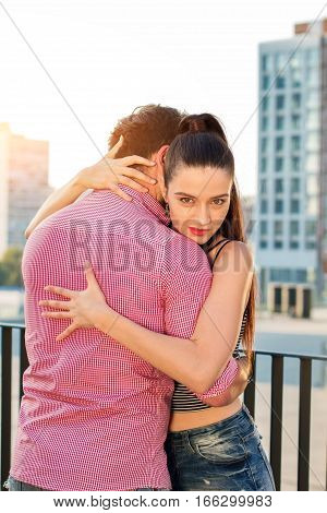 Young lady hugging man. Romantic couple at daytime. Youth and love.